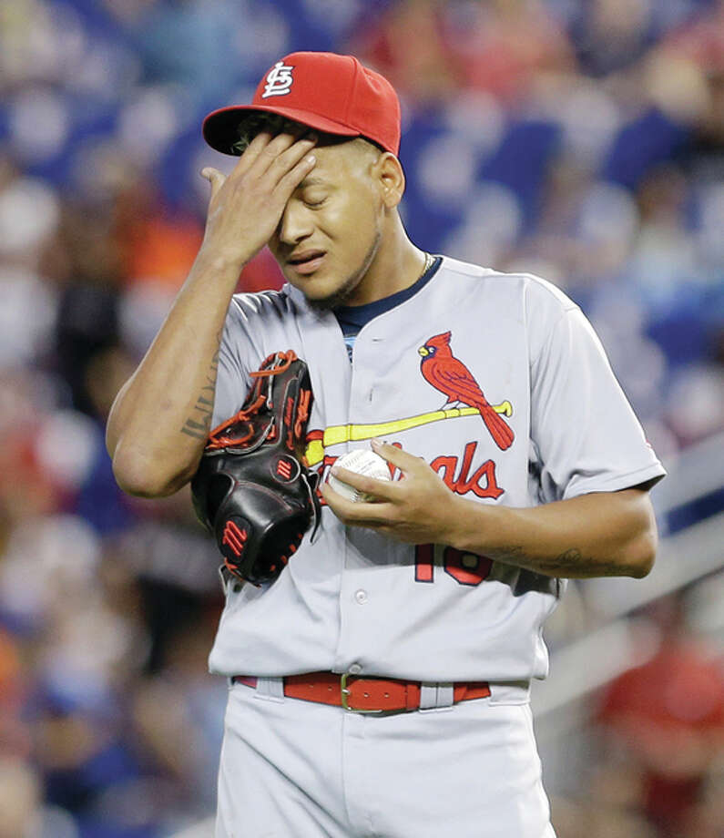 Cardinals pitcher Carlos Martinez wipes his face after allowing a double by the Marlins' Marcell Ozuna in the first inning Sunday in Miami. Photo: Associated Press