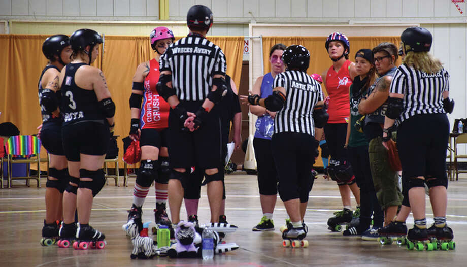 Confluence Crush Roller Derby players huddle before a game. The roller derby group has worked its way to an international ranking and a membership with the Women's Flat Track Derby Association. Photo: Katelyn Petrin|For The Telegraph