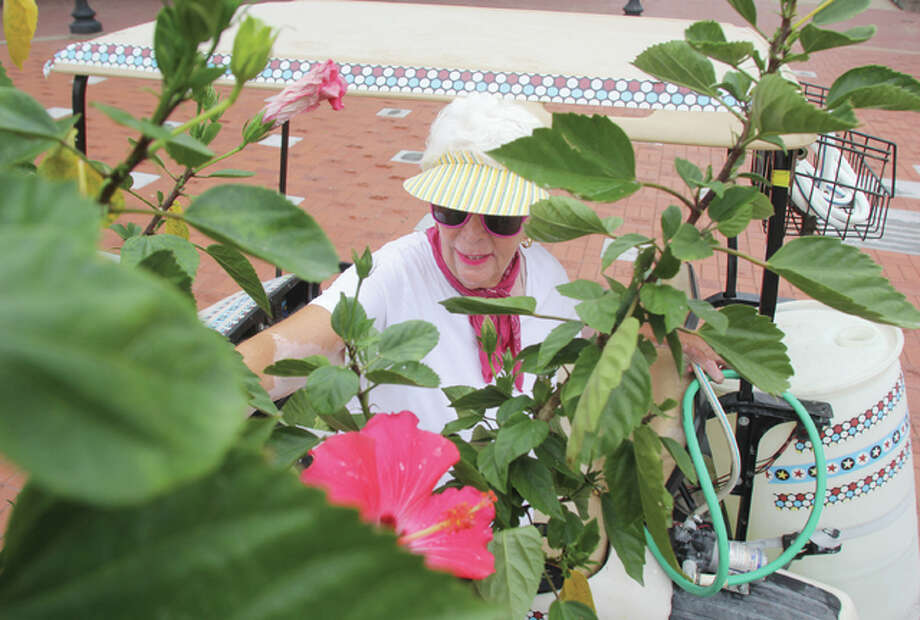 Carolyn MacAfee waters a flowerpot at the Lincoln Douglas Square Tuesday. MacAfee, a 2nd Ward Alderwoman and chair of the Alton Beautification and Clean City Committee, has been watering plants on Broadway and downtown for more than three years.