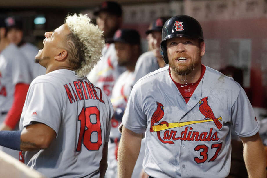 Thye Cardinals' Brandon Moss (right) celebrates in the dugout with Carlos Martinez (18) after hitting a solo home run during the eighth inning Tuesday in Cincinnati. Photo: Associated Press