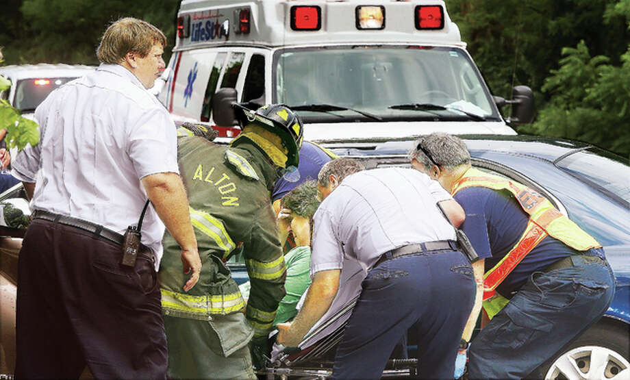 Alton firefighters and LifeStar Ambulance paramedics tend to the injured driver of a GMC Terrain Wednesday after it collided head-on with a Hyundai Sonata, killing a woman who was in the Sonata.