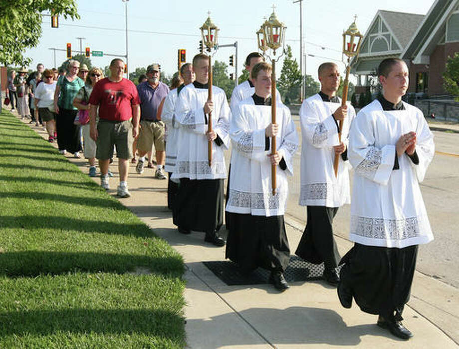 In this July 17 photo, a group of servants lead a procession in Quincy to mark the 130th anniversary of Father Augustus Tolton's return to the city after his studies and ordination in Rome. When the Rev. Tolton returned to Quincy in 1886, hundreds of Quincyans welcomed home the country's first recognized black priest with open arms. This years celebration, a much smaller, but no less reverent, crowd marked the anniversary with prayer and a procession to St. Peter Catholic Cemetery, where Tolton has been buried for almost 120 years.