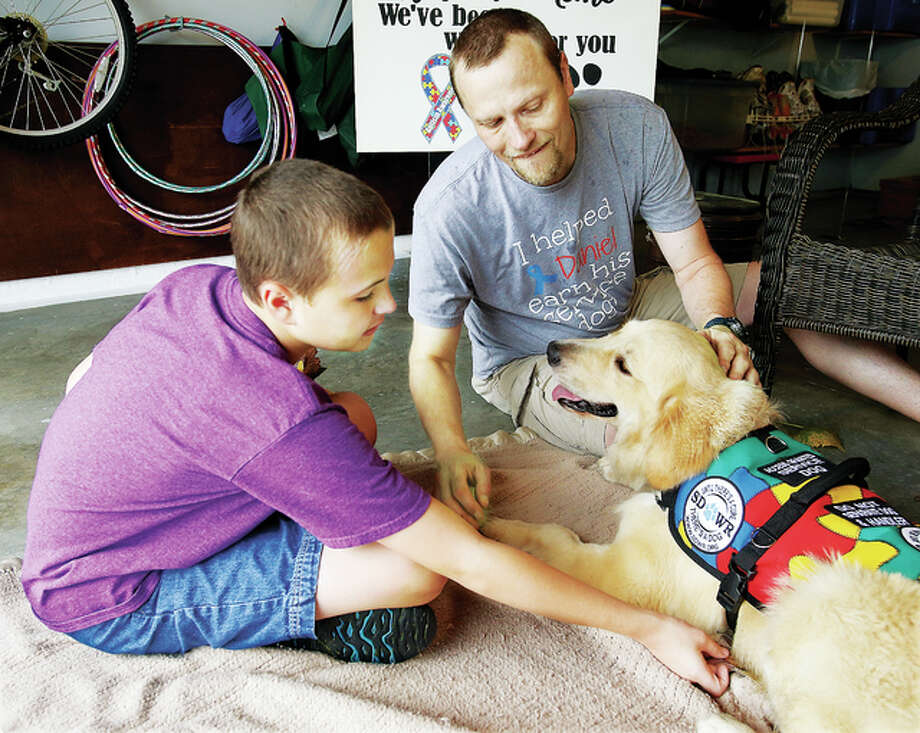 Daniel Salvato, 12, reaches out to his new support dog, Wags, with his dad, Andrew, Friday morning after the dog arrived at their Godfrey home. Wags, a 1-year-old male golden retriever, is a specially trained autism service dog who will undergo several days of training now with his new family.