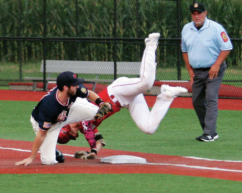 Edwardsville's first baseman Maverick McSparin (left) gets tangled up with Pickerington's Mitch Lohr on a play at first base in the first inning Wednesday night during the 2016 Great Lakes Regional at SIUE's Roy E. Lee Field in Edwardsville. McSparin had to leave the game with a knee injury that ended his tournament. Photo: James B. Ritter / For The Telegraph