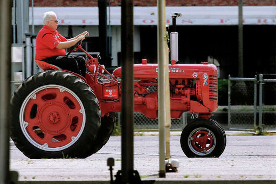 In this Thursday photo, Mike Hall drive a antique International Harvester Model C tractor near the horse barns at the Illinois State Fair in Springfield, Ill. The Illinois state budget mess has come home to roost at the Illinois State Fair, where admission is up 40 percent and for the first time, attending the Aug. 11 preview night is no longer free.