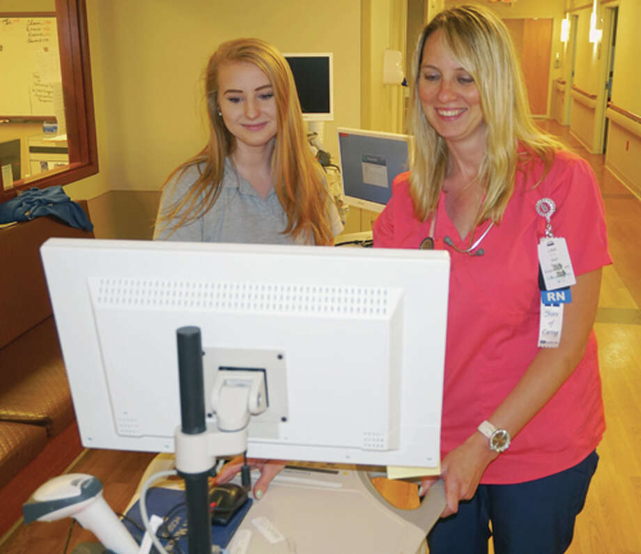 Edwardsville High School student Mikayla Fry, left, looks over some information on a computer with Lisa Roach, a nurse on Alton Memorial Hospital's Surgical Care Unit. Photo: For The Telegraph