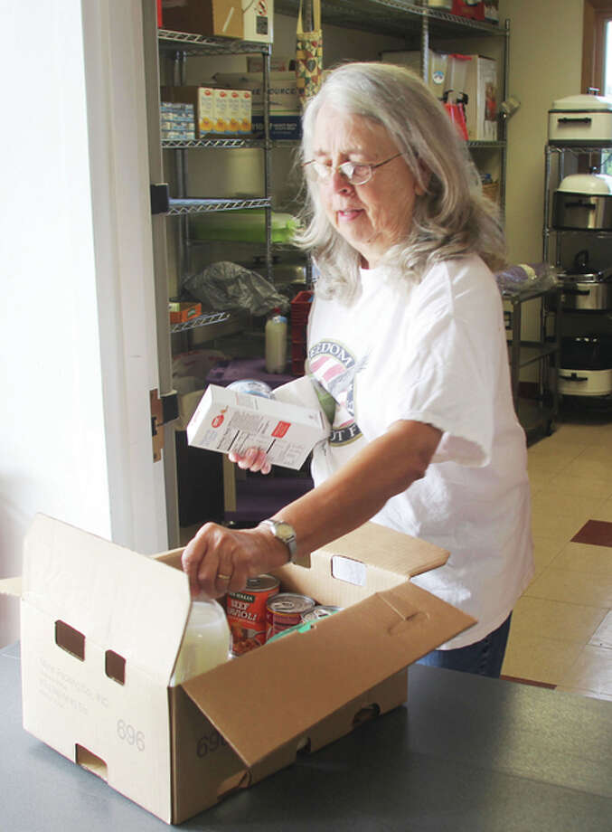 Marilyn King, of Godfrey, prepares boxes for the bi-monthly College Avenue Presbyterian Church's food pantry. The congregation formerly located at Upper Alton's College Avenue Presbyterian Church moved to Wood River's United Presbyterian Church at 2550 E. Rock Hill Road. A vote about whether to merge the two congregations is expected to take place in the near future.