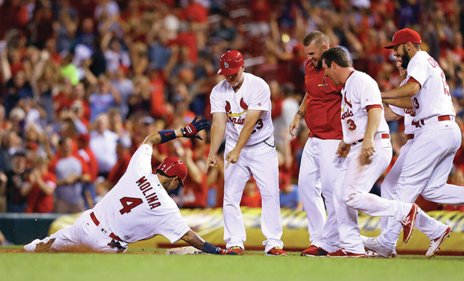 The Cardinals' Yadier Molina (left) celebrates a walk-off victory over the Cincinnati Reds by sliding into first base while teammates approach to join the celebration after Molina was hit by a pitch with the bases loaded in the ninth inning Monday night at Busch Stadium. Photo: Billy Hurst / Associated Press