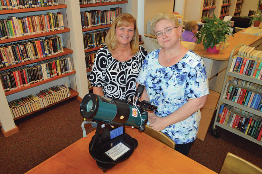 "Hayner Public Library District's Sharon Windham, youth and young adult manager and outreach coordinator, left, and customer service manager Penny Noble for Hayner's downtown branch, lead the telescope program and astronomy related ""parties"" that are held periodically at the library. Vicki Bennington/For The Telegraph"