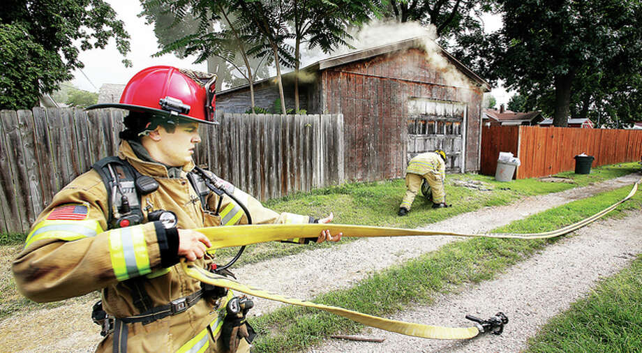 East Alton firefighters, working from the alley behind the garage, pull a hose line into place, preparing to cut through the locked rear door of the garage.