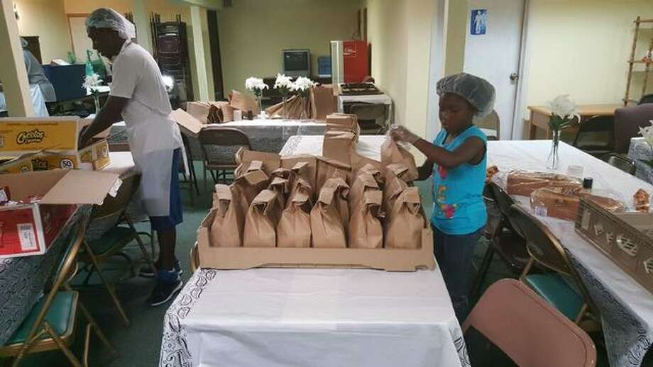 Ava Harris helps out bagging lunches for My Brother's Keeper summer meal program for children, which ends Friday. Submitted art.