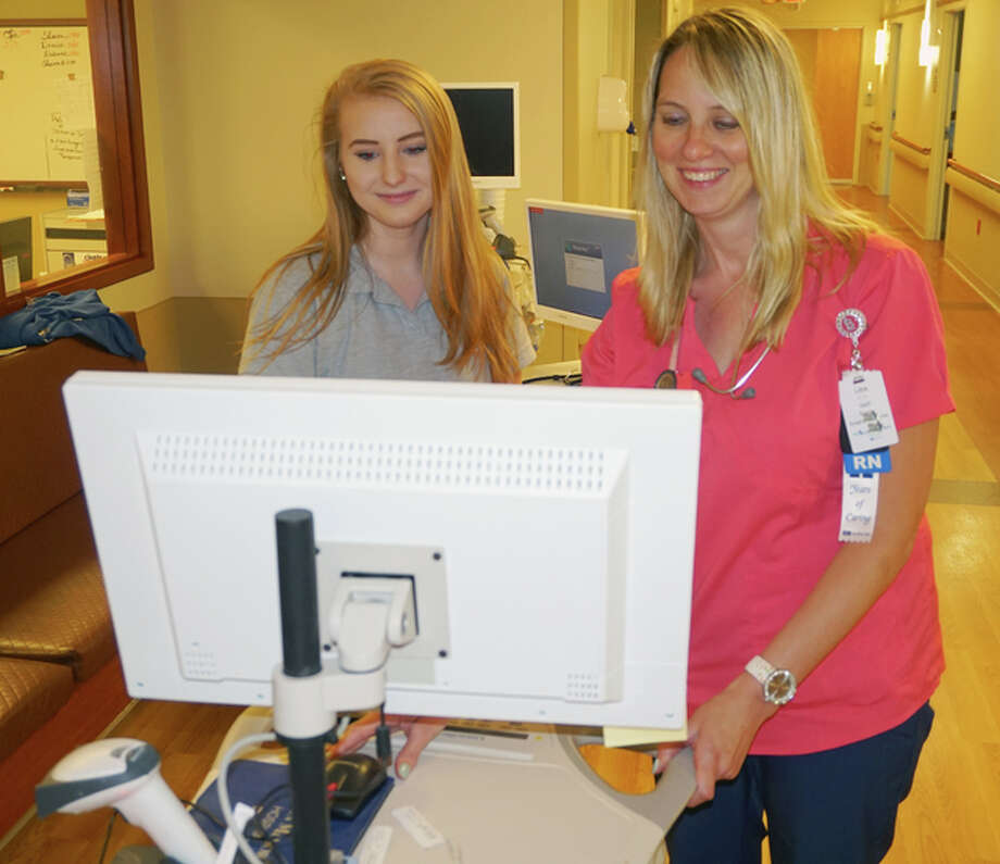Mikayla Fry, left, of Edwardsville High School looks over some information on the computer with Lisa Roach, a nurse on Alton Memorial Hospital's Surgical Care Unit.