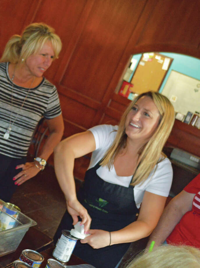 Peggy Bensman, left, listens as Dr. Katie Drake Sherer offers ideas on how to speed up meal preparation. Dr. Katie Drake Sherer and Michael Moginot conduct a Dr. Katie's Kitchen meal preparation party in the dining area at Big Muddy Pub in Alton. Photo: Photos By Vicki Bennington
