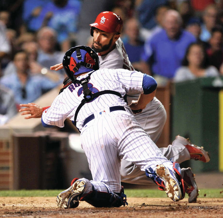 Cubs catcher David Ross tags out the Cardinals' Matt Carpenter (back) at home plate during the seventh inning Thursday night at Wrigley Field in Chicago. The Cubs beat the Cards 4-3 in 11 innings. Photo: Associated Press