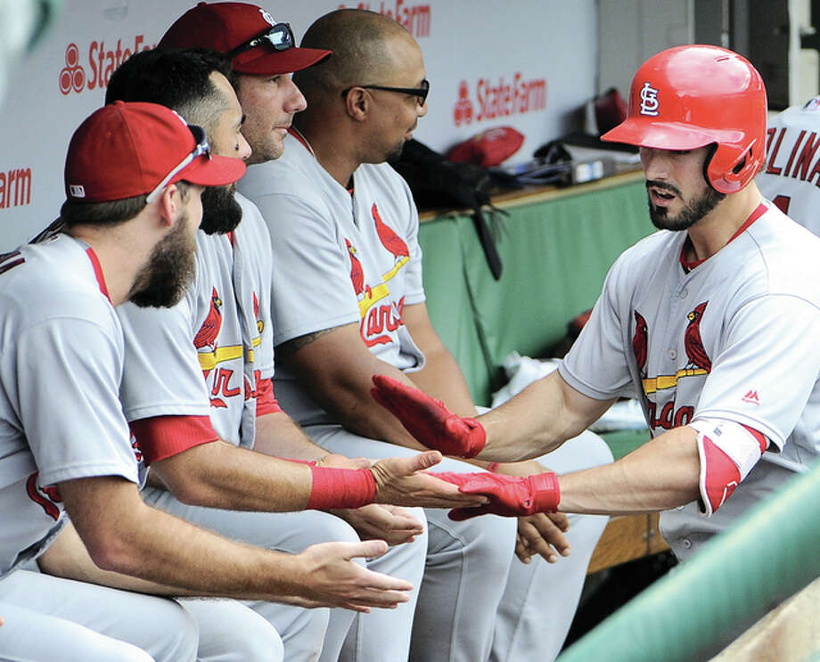 The Cardinals' Randal Grichuk (right) is greeted by his teammates in the dugout after hitting a grand slam against the Cubs during the eighth inning Saturday at Wrigley Field in Chicago. Photo: Associated Press