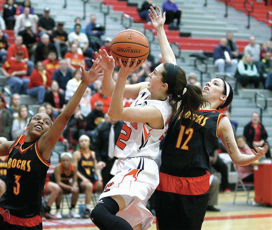 Edwardsville's Makenzie Silvey (middle) goes up to score between Rock Island defenders T'Nauzhae Robinson (left) and Mariah Hoover during the Tigers' Class 4A sectional championship game victory at Alton High in Godfrey. Silvey, a 5-foot-11 guard, has committed to play Division I college basketball at SIUC. Photo: Scott Kane / For The Telegraph