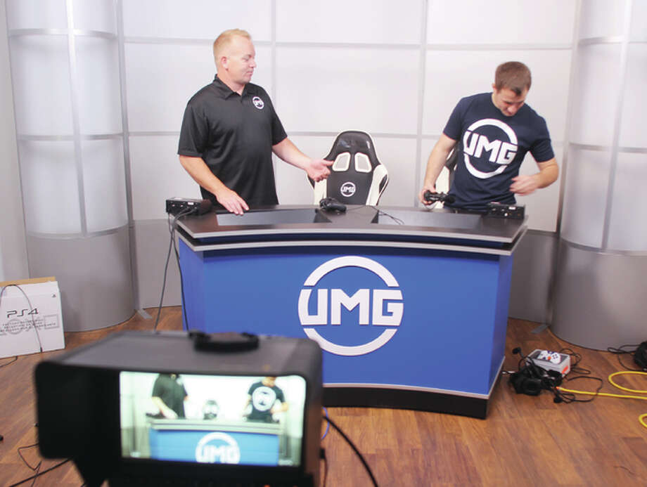 Jeff Covington, left, chief executive officer of UMG Events LLC, an Alton-based eSports company, and studio manager Taylor Noble, work in the company's new broadcasting studio at their Alton office.
