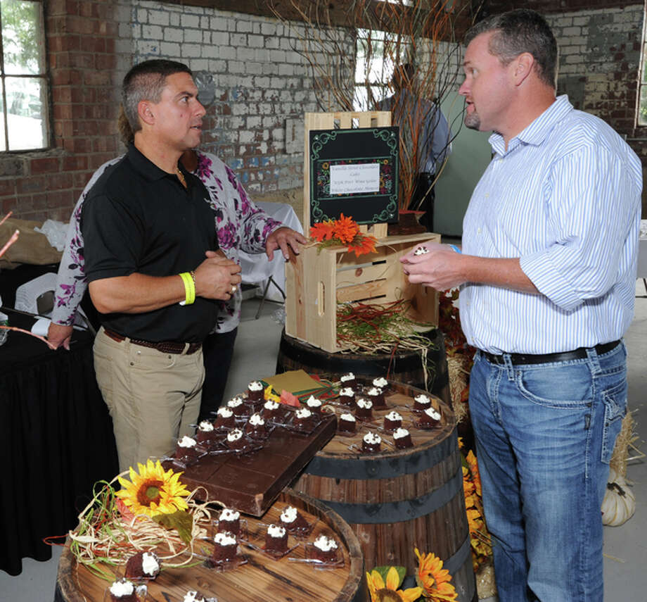 """Bob Menichino, left, of Morrison's Food and Nutrition Services at Alton Memorial Hospital, speaks with Brad Goacher, AMH vice president of Operations, during the 2015 """"Girls on Grapes, Boys on Brew"""" fund raiser at the Loading Dock in Grafton."""