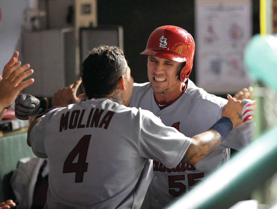 The Cardinals' Stephen Piscotty celebrates with teammate Yadier Molina (4) in the dugout after hitting a three-run home run during the eighth inning to give the Cards a lead against the Chicago Cubs on Sunday night in Chicago. Photo: Associated Press