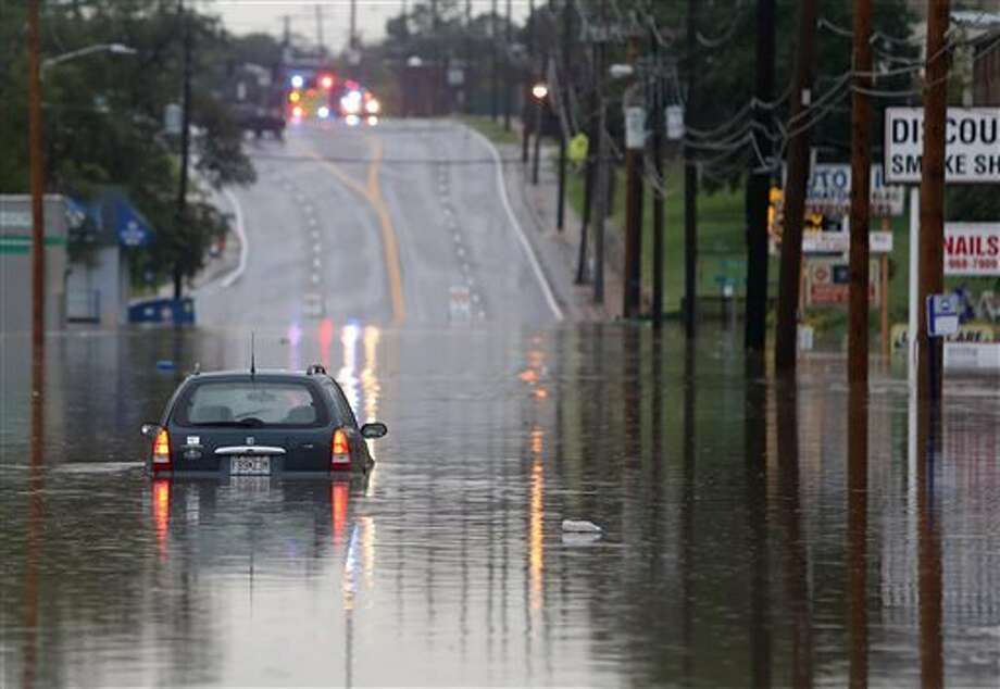 A car sits in the middle of Manchester Road surrounded by floodwater from Deer Creek in Brentwood, Mo., on Monday, Aug. 15, 2016. More than 7 inches of rain in parts of Missouri led to scattered evacuations, power outages and flood warnings. (David Carson/St. Louis Post-Dispatch via AP)