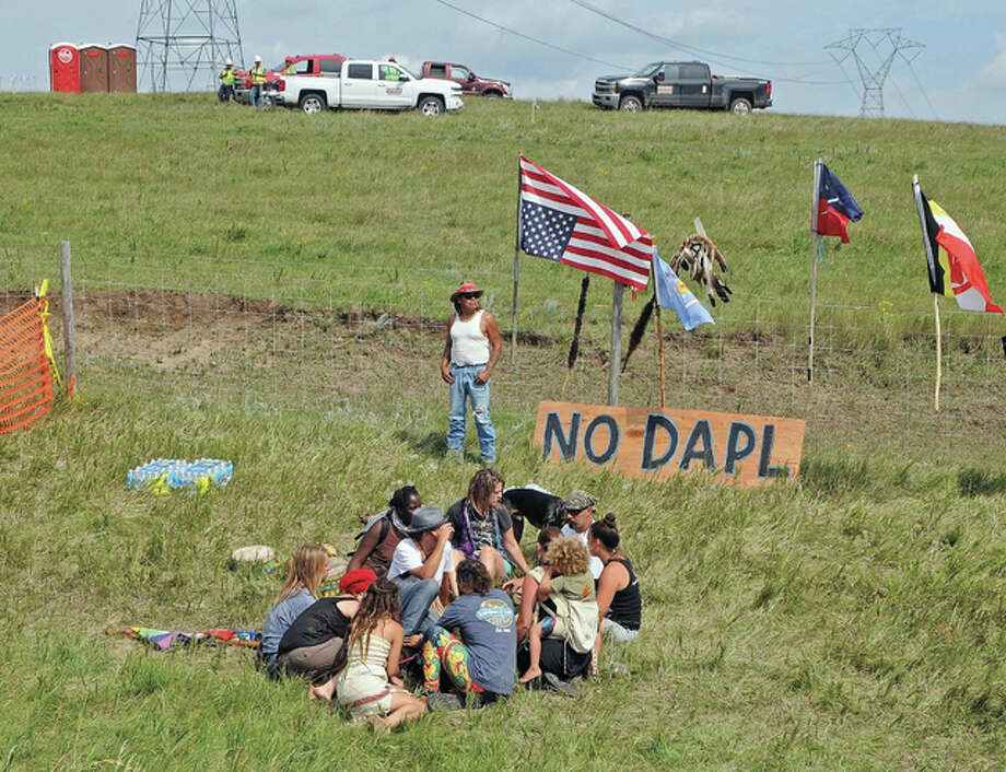Bill Left Hand, of McLaughlin, South Dakota, stands next to a sign at the site of a protest Friday, Aug. 12, against construction of the Dakota Access Pipeline that will cross the Missouri River in Morton County. The pipeline would start in North Dakota and pass through South Dakota and Iowa before ending in Illinois.