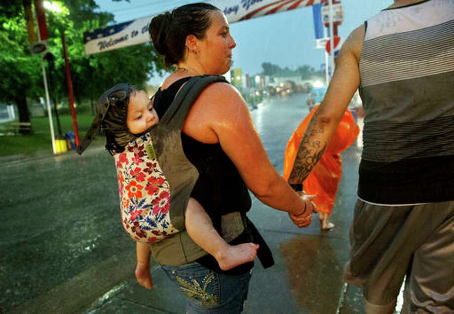 Christi Gaskin carries her daughter Alexia Belcher on her back as she makes her way back to the car with husband Bradley Belcher and her son Dayne during a downpour at the Illinois State Fairgrounds Friday, Aug. 12, 2016 in Springfield, Ill.