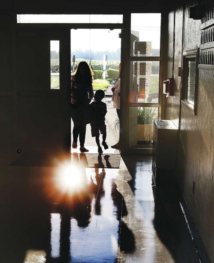 The early morning sun glints off the freshly waxed floors of Lewis and Clark School in Godfrey Thursday morning as a parent walks her child through the front door on the first day of classes in the Alton School District. A major shift in Alton this year converted the elementary schools from neighborhood schools to grade level centers with Lewis and Clark now teaching pre-school, kindergarten and first grade students only.