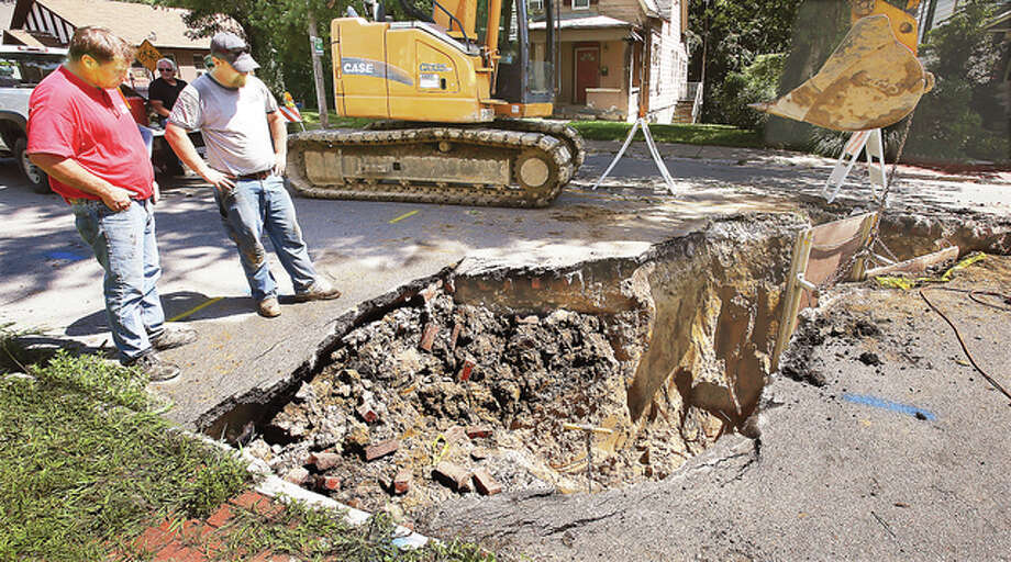 Workers were on the scene of a large sinkhole Thursday on West 9th Street in Alton just south of State Street. Erosion caused by a broken sewer lateral line caused the cave in which was big enough to swallow a car.