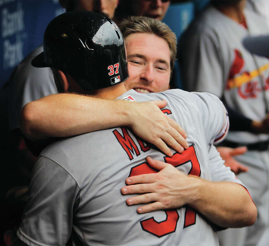 The Cardinals Brandon Moss is embraced by teammate Jedd Gyorko (facing) after Moss homered in the fourth inning Sunday in a win over the Phillies in Philadelphia. Photo: Associated Press