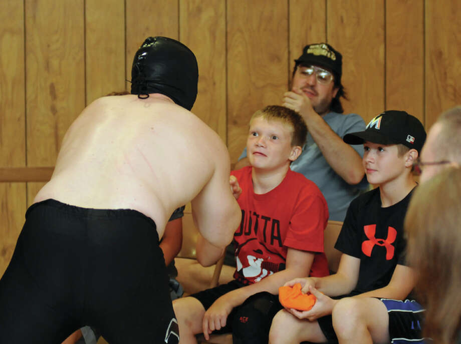 A young fan seems at once fascinated and a bit scared by a wrestler working the crowd during the Dynamo Pro Wrestling event this weekend in Wood River. With modern pro-wrestling fans can have that good and evil mentality.