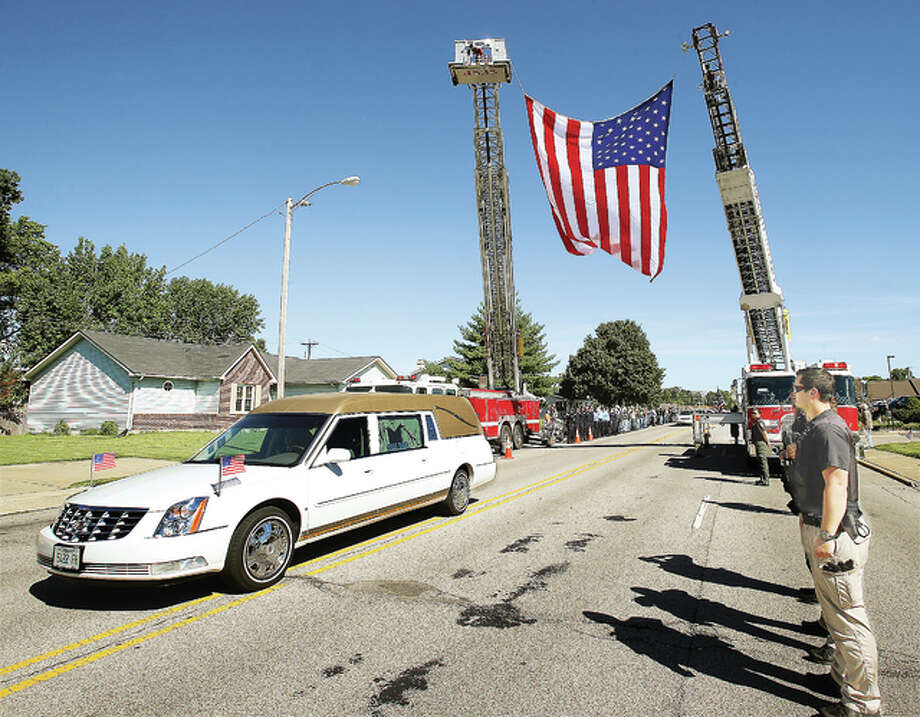 The hearse carrying Staff Sgt. Christopher Wilbur passes under a large American flag held up by fire department ladder trucks from Granite City and Madison as the hearse nears Irwin Chapel on Maryville Road in Granite City Monday. Wilbur, 36, died in Kandahar, Afghanistan on Aug. 12, from a non-combat injury for which no details have been released by the U.S. Department of Defense. Regional police officers and firefighters stand at attention as the hearse passes by. Photo: John Badman|The Telegraph