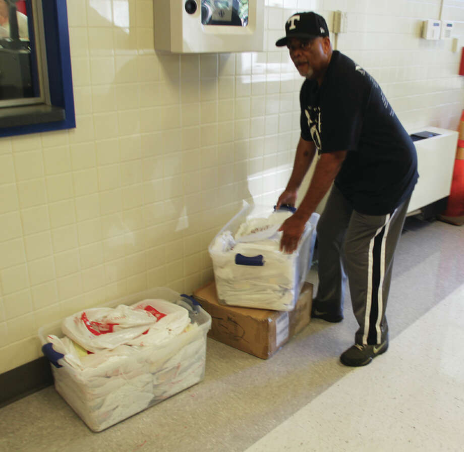 Alton NAACP chapter President James Gray stacks school supplies at East Elementary School Monday morning. NAACP officials brought 250 backpacks and other supplies to five Alton elementary schools Friday and Monday. Photo: Scott Cousins/The Telegraph