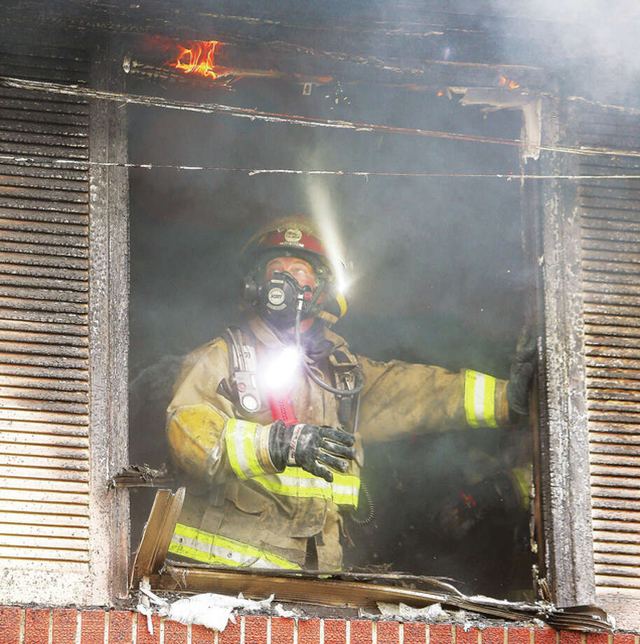 A firefighter looks up at flames burning on the window frame of an upstairs apartment Tuesday in the 500 block of Grove Avenue in Wood River where a fire engulfed one end of a multi-unit apartment building. Flames were roaring from two windows when police and firefighters arrived. A resident was reportedly burned but could not be initially located. Officials believe the resident found their own way to treatment. Firefighters from Wood River, Roxana, East Alton, Edwardsville and Alton were called to the scene to assist. Photo: John Badman | The Telegraph