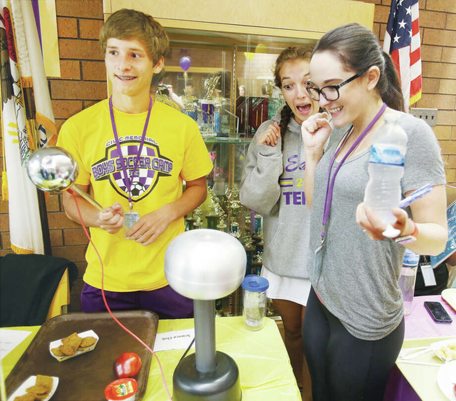 Civic Memorial High School students had a chance to learn about and join clubs and organizations in the school cafeteria Tuesday. Crista Stover, right, of the Life Savers Club, reacts after getting a mild shock from Van De Graaff generator, a device that produces static electricity, set up by Science Club members Kameron Denney, left, and Morgan Butler, center.