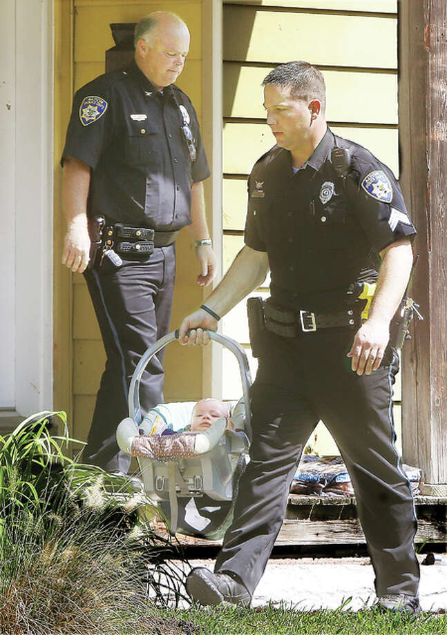 Alton Police Sgt. Kurtis McCray carries a 7-month-old baby boy out of a house Thursday morning in the 300 block of Bluff Street in Alton solving a morning mystery for police. Alton Police Chief Jake Simmons follows McCray. The complicated ordeal began with a domestic dispute between the baby's mother and father in the 600 block of Olmstead Way in Alton after the man smashed the windows out of the mother's car with a baseball bat. The man then apparently handed off the child to a third-party female who took the baby from the area. Multiple police units were searching for the child. The father was located and arrested later in the morning and police were able to recover the baby unharmed on the other side of Alton.