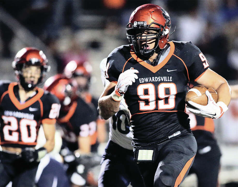 Edwardsville's AJ Epenesa (99), shown returning a fumble for a touchdown in a Tigers win over Belleville East last season, begins his senior season as one of the nation's highest-ranked players on Friday night at Quincy. Photo: Scott Kane / For The Telegraph