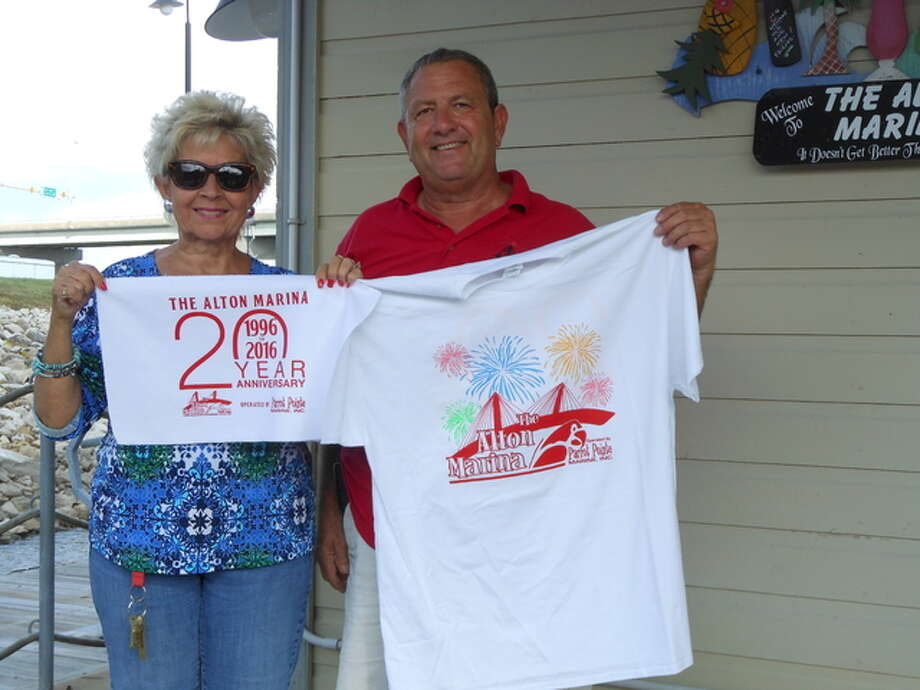 Alton Marina General Manager Karen Baker-Brncic and Harbormaster Greg Brown hold a special, commemorative rally towel and T-shirt in preparation for Saturday's festivities celebrating the marina's 20th anniversary.