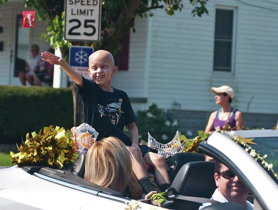 Jonny Wade, an 8-year-old from Jerseyville who battled Medulloblastoma, a type of brain cancer, entertains his fans and tosses candy in September of 2015 while performing his duties as this year's grand marshal in the Bethalto Labor Day Parade.