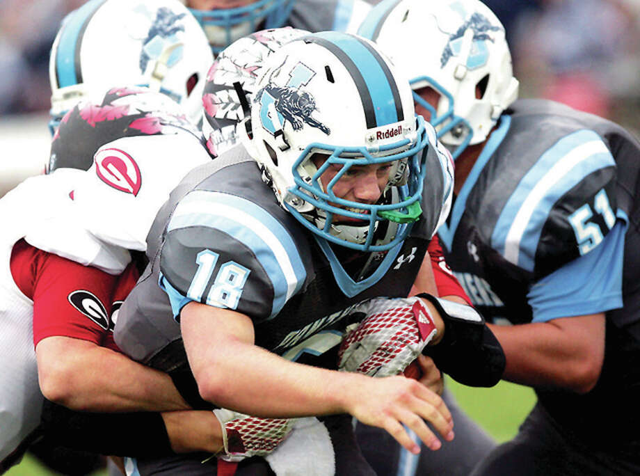 Jersey quarterback Drew Sauerwein gets swallowed up by a pair of Granite City defenders as he tries to scramble Friday night in Jerseyville. Photo: James B. Ritter | For The Telegraph