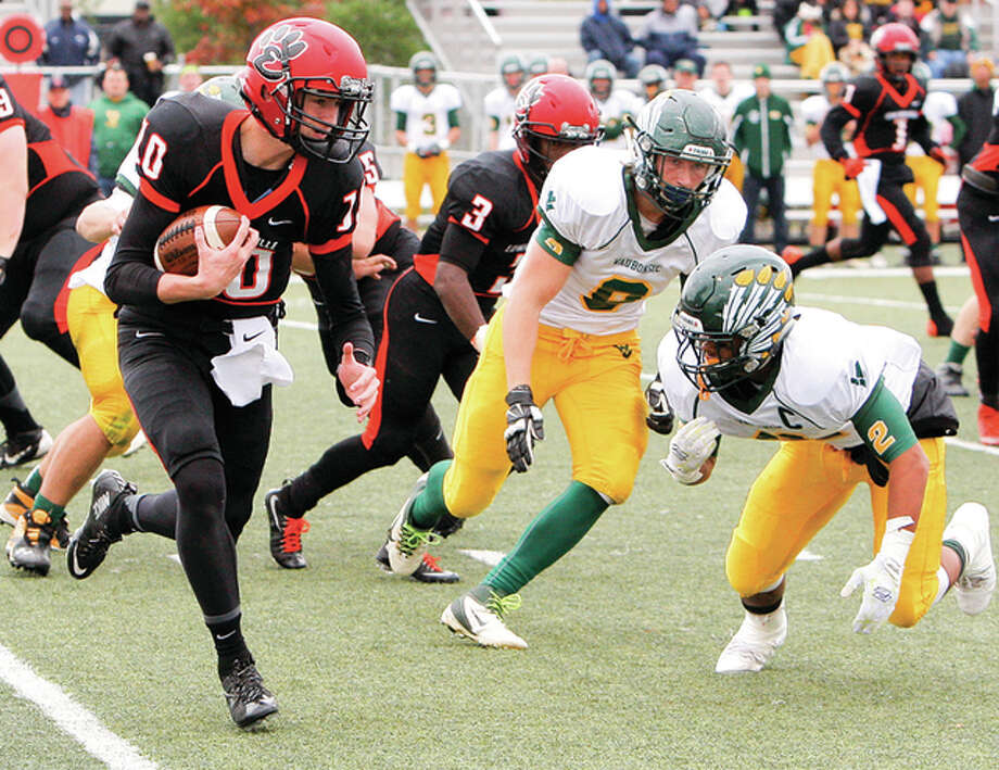 Edwardsville quarterback Brenden Dickmann (left), shown scrambling with the ball against Waubonsie Valley in a Class 8A playoff game at Edwardsville, opened his senior season by helping the Tigers to a 35-6 victory in Quincy. The game was halted by lightning Friday and completed on Saturday night. Photo: Scott Kane / For The Telegraph
