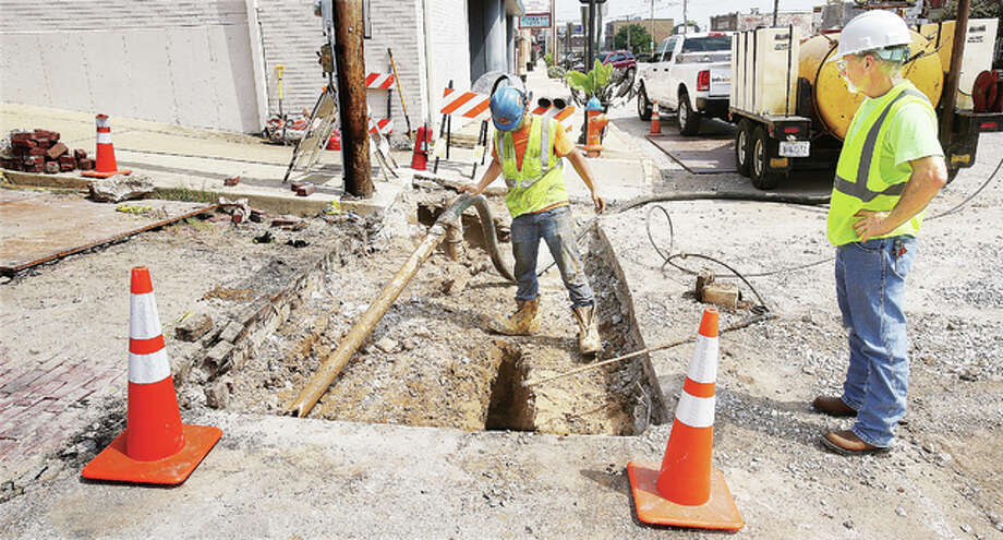 Workers were still sucking muddy water out of a hole they made in the street at East Broadway and George Street in Alton Monday. The hole is the result of Ameren's 5,000-foot-long natural gas pipeline replacement project. Photo: John Badman|The Telegraph