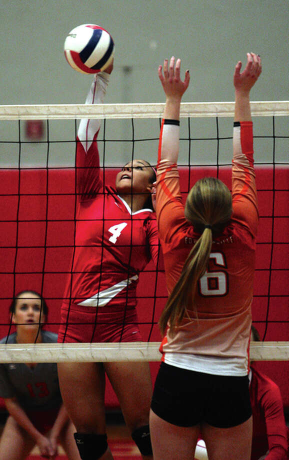 Alton's Savannah Fisher (left), shown hitting past the block against Edwardsville last season, returns for her senior season to lead a Redbirds team taking aim at a third straight 20-win season. Photo: James B. Ritter / For The Telegraph