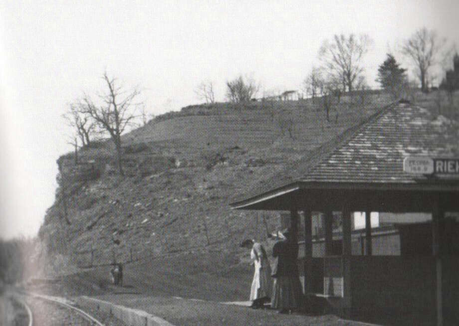 Two women stand on the platform of Riehl's Station, named for early Godfrey resident E.A. Riehl, located in present-day Godfrey Township at the Madison-Jersey county line. The Great River Road replaced the local passenger train line in the 1940s. Photo: Source: Images Of American: Godfrey