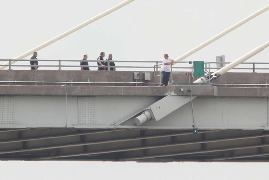 Police officers talk to a woman standing outside the guardrail on the Clark Bridge at about noon Wednesday. Police were eventually able to talk the woman into coming back onto the bridge deck at about 12:30 p.m.