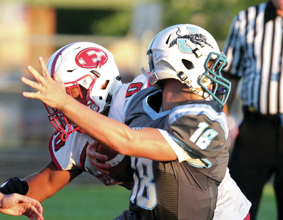 Jersey quarterback Drew Sauerwein has his helmet turned around backwards by Effingham's Noah Spencer Friday night in Jerseyville. Spencer was called for a face mask penalty on the play, keeping a Jersey drive alive. Photo: James B. Ritter | For The Telegraph