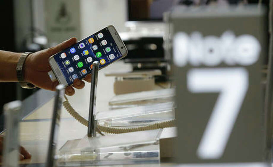 A customer holds a Samsung Electronics Galaxy Note 7 smartphone at the headquarters of South Korean mobile carrier KT in Seoul, South Korea, Friday. Samsung will issue a global recall of the Galaxy Note 7 smartphone as soon as this weekend after its investigation on explosion claims found batteries were at fault, according to South Korea's Yonhap News.