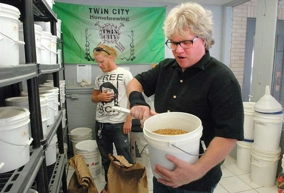 In this Aug. 11, 2016 photo, Dylan Karraker, left, and his father, Kyle, manage the variety of hops that are sold at their Twin City Home Brewing Beer and Wine supply store in Bloomington, Ill. More than 1.2 million people brew their own beer at home in the United States, according to the American Homebrewers Association. Karraker said his store, which has between 75 to 100 regular customers, saw a 20 percent growth in its client base between this year and last. (David Proeber/The Pantagraph via AP)