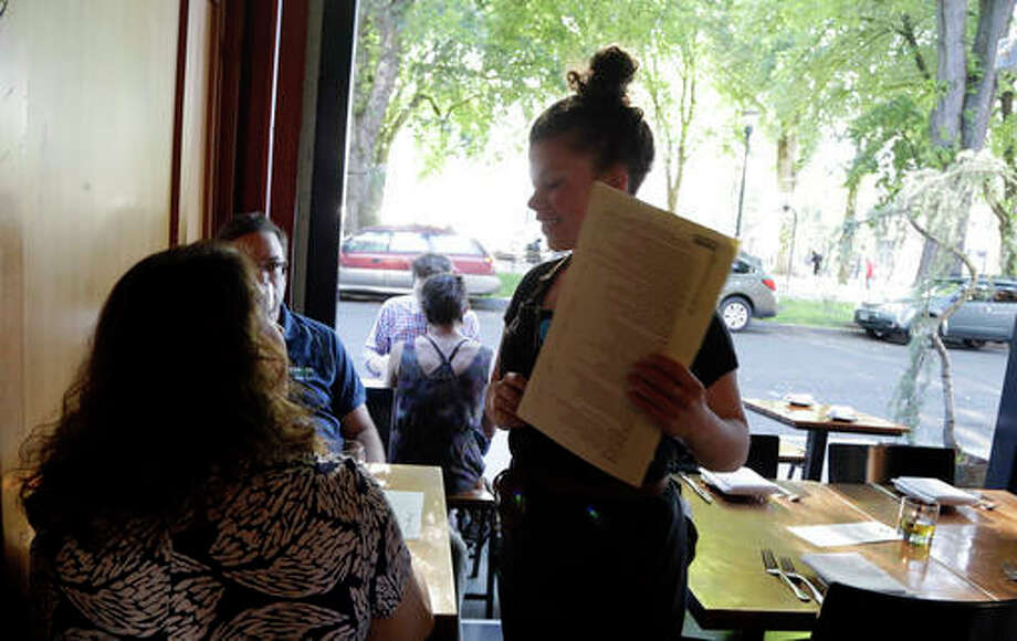 In this Monday, Aug. 8, 2016, photo, Caroline Pond, who serves as sous chef, server and bartender, talks with customers to their table at Park Kitchen restaurant in Portland, Ore. A small but growing number of restaurants are doing away with the tipping model that has long been the norm in the U.S. in an effort to even disparate pay among restaurant staff, as well as a means to cope with rising minimum wages and other industry changes. (AP Photo/Don Ryan)