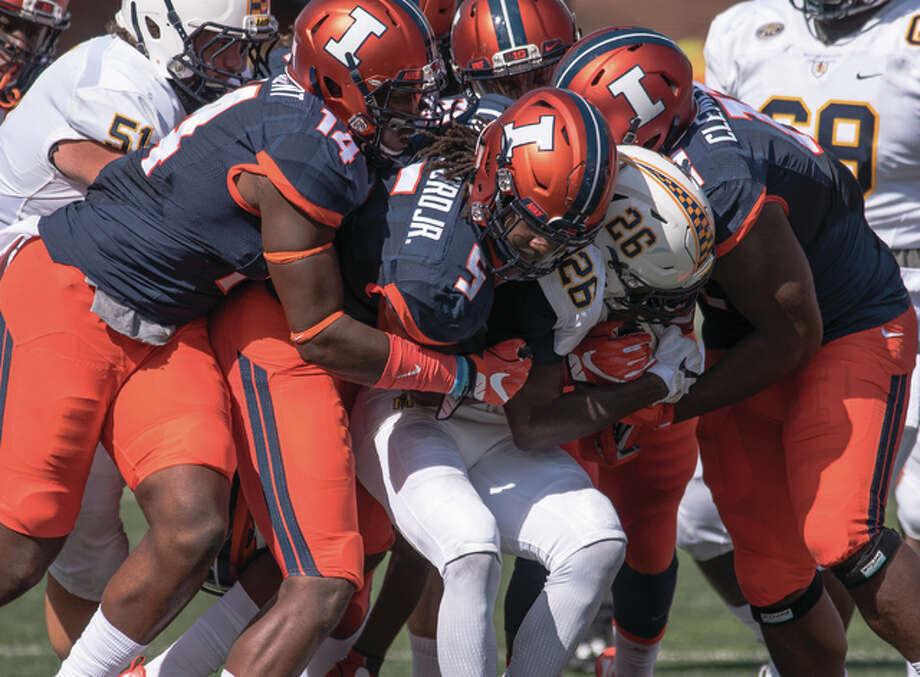 Murray State running back Demetric Johnson (center) is tackled by Illinois linebacker James Crawford (5), defensive lineman Gimel President (14), and defensive lineman Chunky Clements (11) during the second quarter Saturday at Memorial Stadium in Champaign. Photo: Associated Press