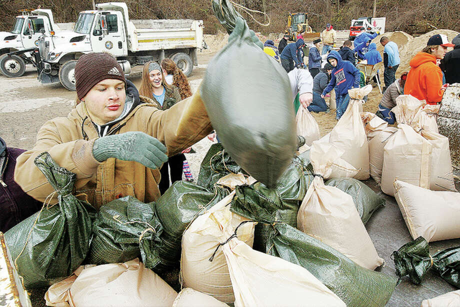 John Badman|The Telegraph Volunteers load and fill sandbags in downtown Alton during the height of the fourth worst flood in the city's history in December of 2015.